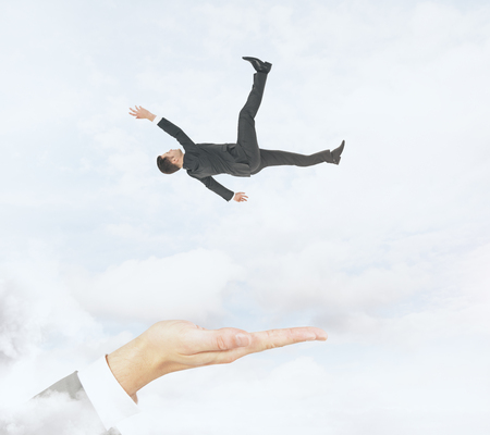 Hand ready to catch falling businessman on cloudy sky background. Assistance and risk conceprt
