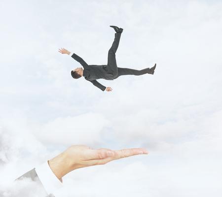 Passi pronto a prendere l'uomo d'affari di caduta sul fondo del cielo nuvoloso. Assistenza e concezione del rischio Archivio Fotografico - 91782267
