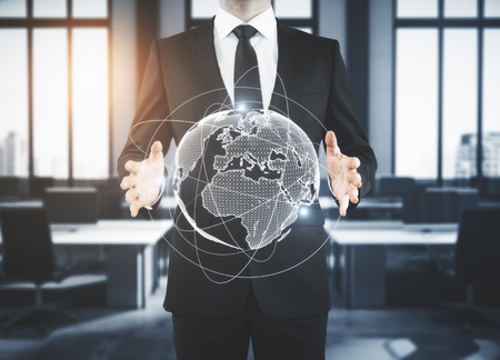 Businessman holding polygonal globe on blurry office interior background. Global business concept. 3D Rendering