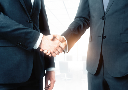 Side view of handshake on abstract blurry bright office background. Teamwork and collaboration concept