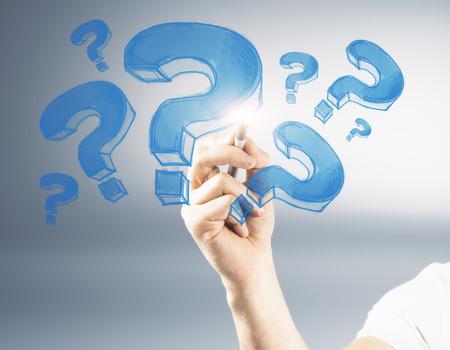 회색 배경에 파란색 물음표를 그리기 남성 손. FAQ 및 혼동 개념