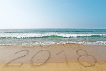 Beach backdrop with wave washing away year 2017 and revealing 2018. New Year concept
