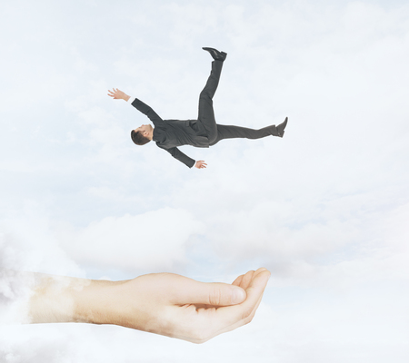Hand ready to catch falling businessman on cloudy sky background. Assistance and help conceprt Stock fotó