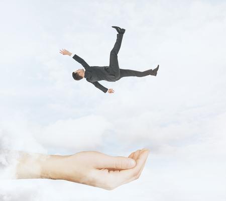 Passi pronto a prendere l'uomo d'affari di caduta sul fondo del cielo nuvoloso. Assistenza e aiuto concepito Archivio Fotografico - 91890284