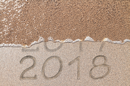 Beach background with wave washing away year 2017 and revealing 2018. New Year concept