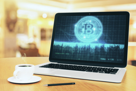 Close up of laptop with creative bitcoin chart on screen placed on wooden desktop with coffee cup and pen. Blurry bokeh background. E-commerce and economy concept. 3D Rendering  Stock Photo