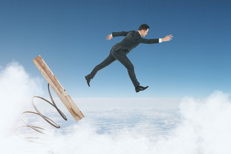 Abstract image of businessman on start up mechanism. Cloudy sky background. Entrepreneurship and forward concept