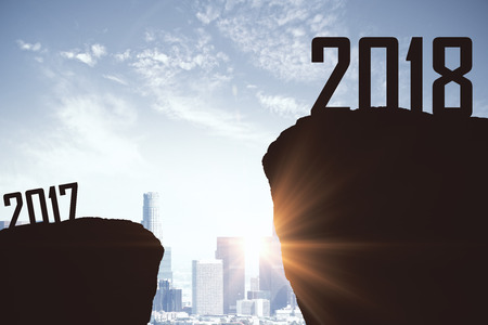Mountain gap between 2017 and 2018 on city backdrop. New Year concept