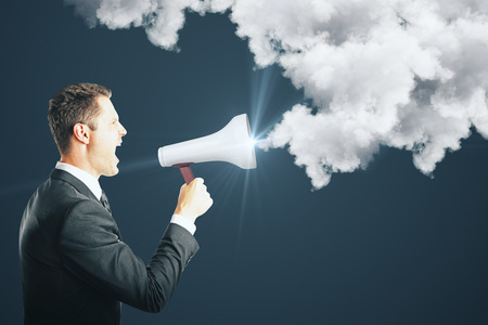 Side view of young businessman screaming into glowing megaphone on dark background with communication cloud. Anger and announcement concept