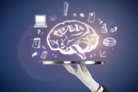 青い背景に脳のスケッチと手持ちトレイ。ブレーンストーミングとマーケティングの概念 写真素材