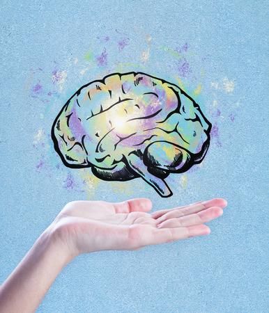 青い背景に脳のスケッチを保持する手。ブレーンストーミングとアートコンセプト 写真素材