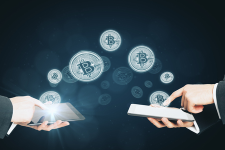 Bitcoins transferring from devices on blurry background. Cryptocurrency and payment concept Stock fotó