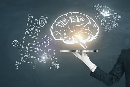 黒板の背景に輝く脳のスケッチを持つビジネスマンの手保持トレイ。インテリジェンスとアイデアの概念