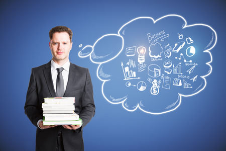 Handsome european businessman holding book stack on abstract background with business sketch in thought bubble. Knowledge and success concept