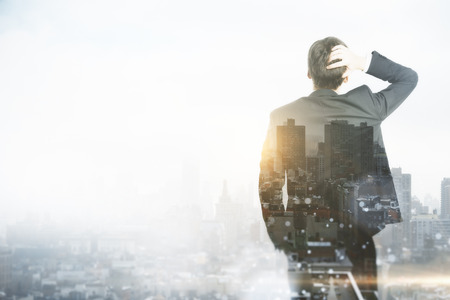 Success and research concept. Businessman standing on abstract city background with copy space. Double exposure