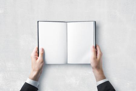 Mão do homem de negócios que guarda o livro aberto vazio no fundo da parede de concreto. Conceito de educação e escola. Brincar
