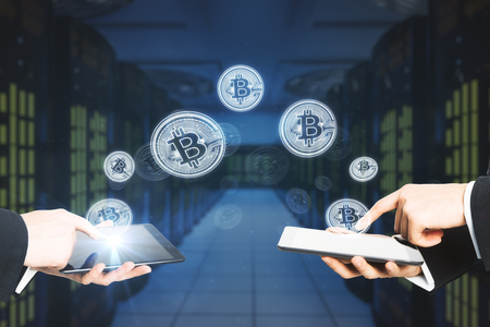 Bitcoins transferring from devices on blurry server background. Cryptocurrency and banking concept Stock fotó - 94388986