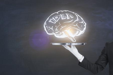黒板の背景に輝く脳のスケッチを持つビジネスマンの手保持トレイ。インテリジェンスとマインドの概念