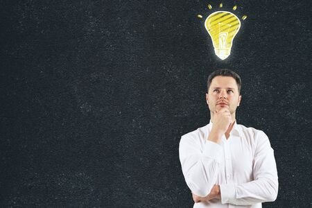 Thoughtful handsome man with draw lamp standing on concrete wall background with copy space. Success and idea concept
