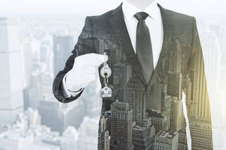 Businessman holding key with house keychain on abstract city background. Mortgage and housing concept. Double exposure  Stock Photo