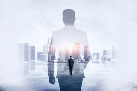 Back view of young businessman walking on abstract city background. Success and development concept. Double exposure  Stock Photo