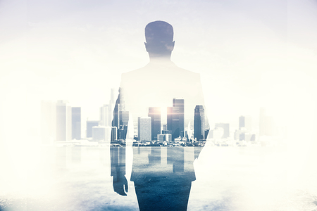 Back view of young businessman walking on abstract city background. Success and career concept. Double exposure