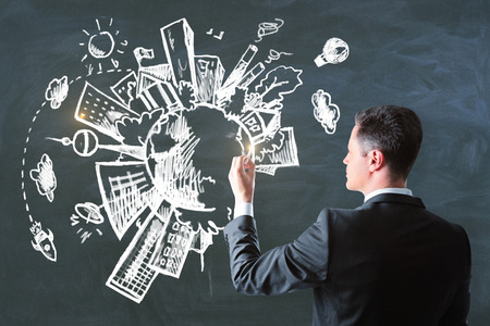 Side view of attractive white man drawing creative eco sketch on concrete wall background. Environment and city concept