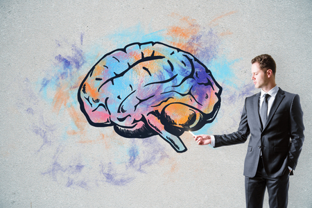 Handsome caucasian businessman drawing creative brain sketch on concrete wall background. Brain storm and leadership concept