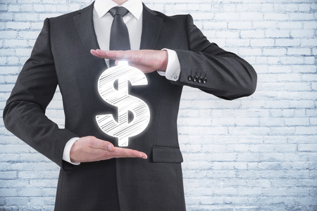 Businessman holding dollar sign on white brick wall background. Investment and money concept