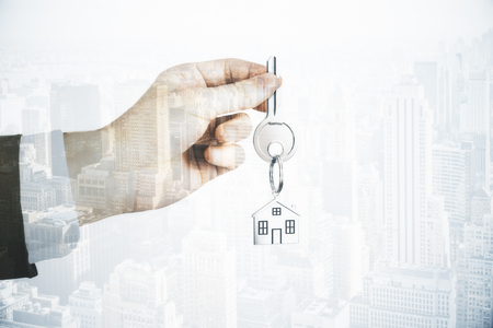 Hand holding key on abstract city background with copy space. Real estate and mortgage concept. Double exposure