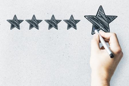 Geschäftsmann, der auf abstrakte Sterne auf Betonmauerhintergrund zeigt. Erfahrungsbewertung und Exzellenzkonzept