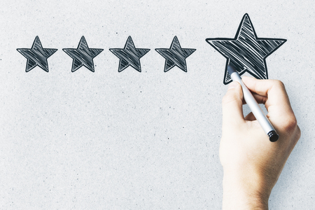 Businessman pointing at abstract stars on concrete wall background. Experience rating and exellence concept