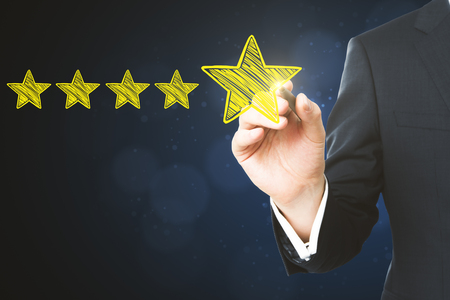Businessman pointing at abstract stars on blurry blue background. Experience rating and ranking concept  版權商用圖片