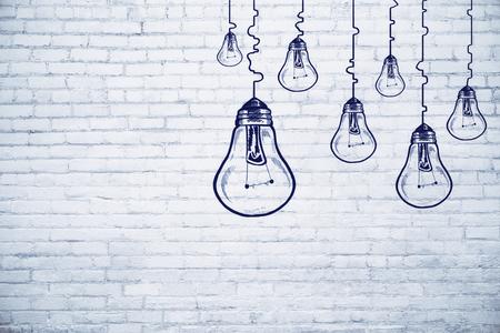 Creative lamp sketch on brick wall background. Idea, innovation and achievement concept  Foto de archivo