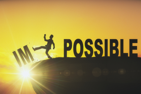 Kicking man silhouette on abstract backlit cliff with text. Impossible is nothing. Motivational backdrop