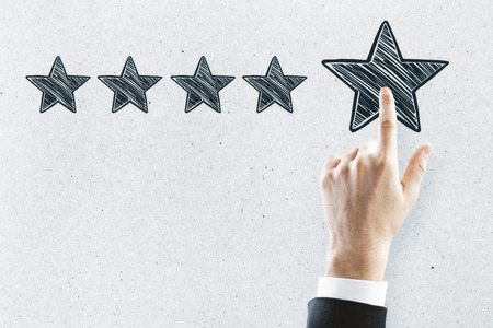 Businessman pointing at abstract stars on concrete wall background. Experience rating and performance concept