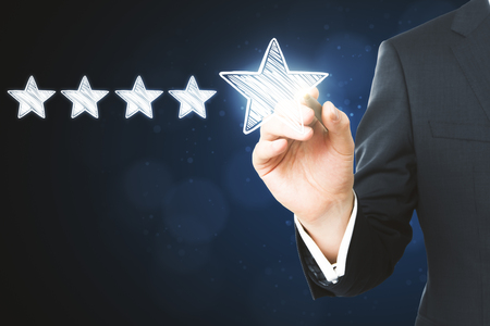 Businessman pointing at abstract stars on blurry blue background. Experience rating and quality concept  Stok Fotoğraf