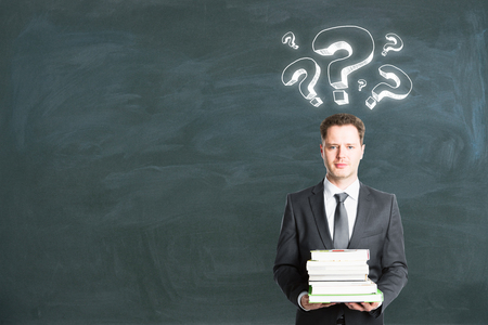 Businessman with question marks holding books on chalkboard background with copy space. Education and faq concept