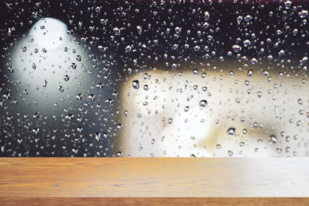 Empty wooden table on blurry rain drop background. Montage concept, Copy space