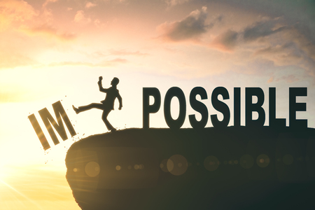 Kicking man silhouette on abstract backlit cliff with text. Impossible is nothing. Motivational background