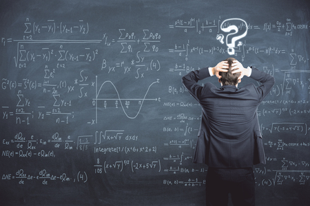 Back view of stressed businessman standing on chalkboard background with mathematical formulas. Science and trouble concept