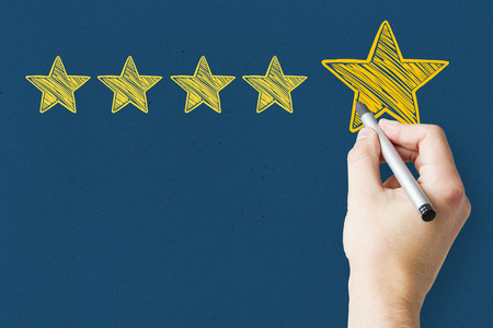 Businessman pointing at abstract stars on blue background. Experience rating and classification concept