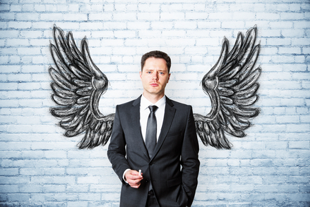 Handsome european businessman on brick background with drawn wings. Leadership and success concept