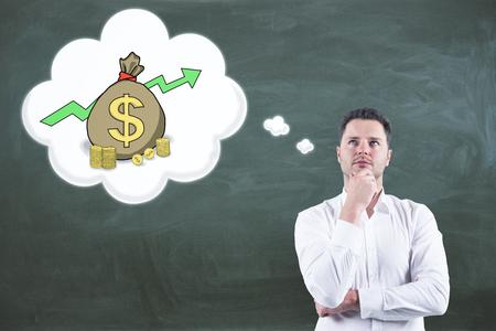Hübscher europäischer Geschäftsmann , der über Geld auf Tafelhintergrund denkt . Finanzen und Investitionskonzept Standard-Bild - 95902644