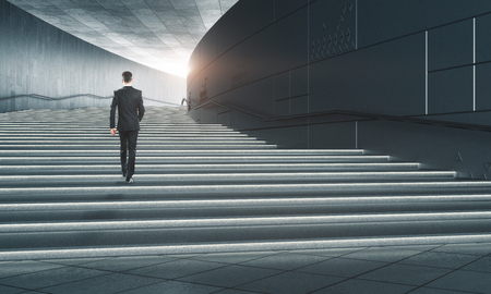 Back view of young businessman climbing concrete stairs leading to sunlight. Success and career development concept. 3D Rendering  Stock Photo