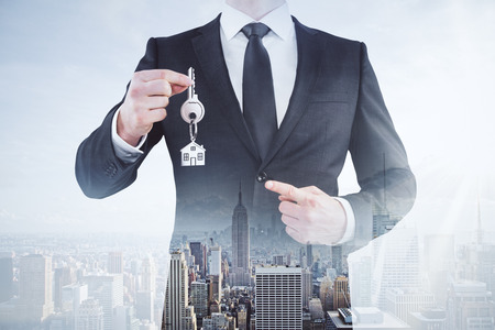 Businessman pointing at key on abstract city background. Real estate concept. Double exposure