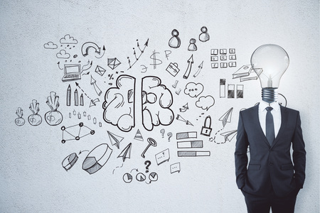 Lamp headed businessman on chalkboard background with business sketch. Idea, solution and brainstorm concept  Stock Photo
