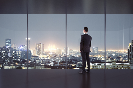 Young man looking out of window in modern office interior with night city view. 3D Rendering