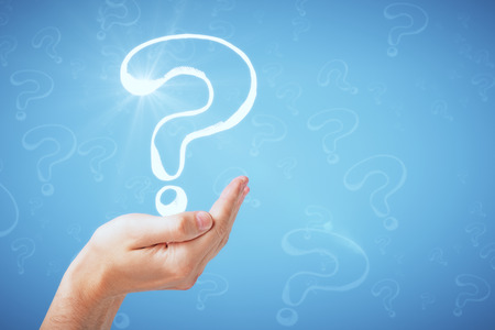 Hand holding question mark drawing on grey background with copy space