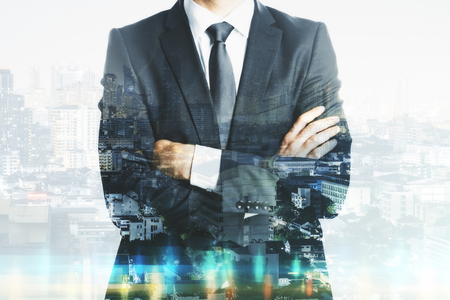 Unrecognizable businessman with folded arms standing on abstract city background with copy space. Employment and success concept. Double exposure